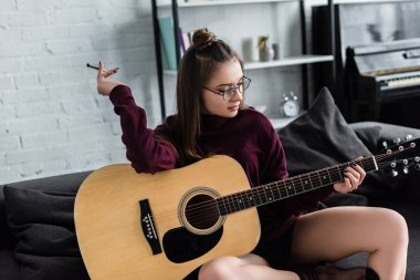 attractive girl sitting, holding marijuana joint and playing guitar at home