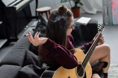 girl sitting, holding marijuana joint and playing guitar in living room