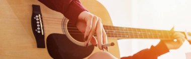 cropped view of girl sitting, holding marijuana joint and playing guitar at home