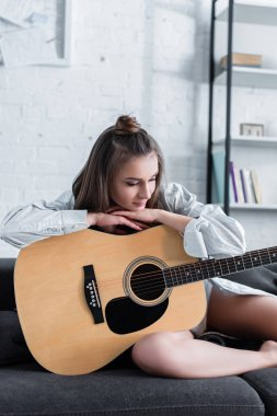 thoughtful musician sitting on sofa and holding acoustic guitar at home
