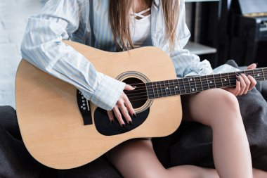cropped view of musician sitting on sofa and playing acoustic guitar at home