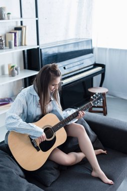 attractive musician sitting on couch and playing acoustic guitar in living room