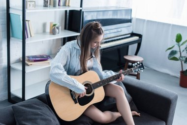 musician sitting on sofa and playing acoustic guitar in living room