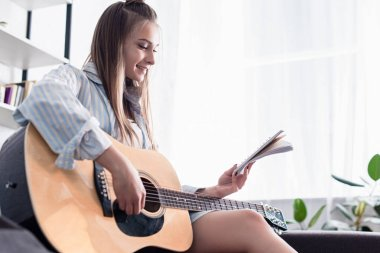 cheerful musician holding notebook and playing acoustic guitar at home