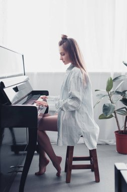 side view of beautiful musician playing piano at home