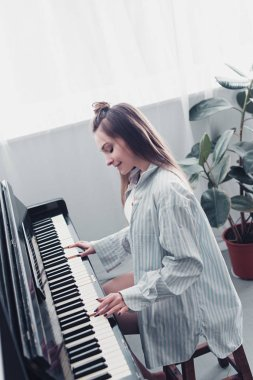 beautiful musician playing piano and smiling in living room