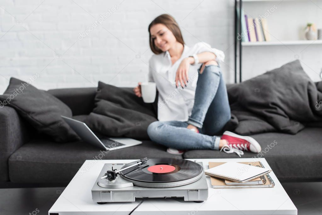 Girl in white shirt sitting on couch with coffee cup, using laptop and listening to vinyl record player in living room stock vector