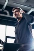 niedrigen Winkel Blick auf schöne Sportler in Hoodie Training auf Laufband und Musikhören im Fitness-Studio