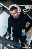 Fotografie vysoký úhel pohled pohledný sportovec v hoodie cvičení na běžeckém pásu a drží láhev sport v tělocvičně