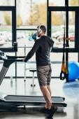 Rückansicht des Sportlers im Hoodie stehen in der Nähe von Laufband mit Flasche Sport im Fitness-Studio