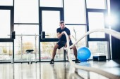 teljes hosszúságú, a jóképű sportoló képzés a tornateremben kötelek