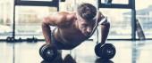 pohledný sportovec shirtless trénink s činkami a dělá prkno v tělocvičně