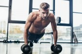 Photo handsome muscular sportsman training with dumbbells and doing plank in gym