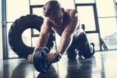 hezký sportovní košili sportovce cvičení s abs roller v tělocvičně