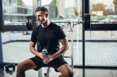 pohledný sportovec odpočívá a drží sportovní láhev vody v tělocvičně