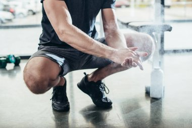 Cropped image of sportsman applying talcum powder on hands before training in gym stock vector