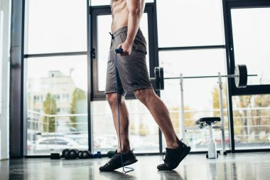 low section of shirtless sportsman training with jumping rope in gym