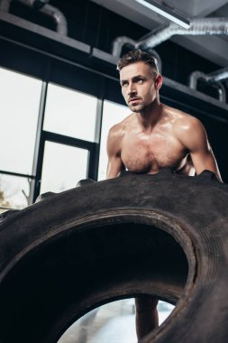 Handsome shirtless sportsman lifting heavy tire in gym stock vector