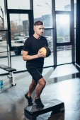 handsome sportsman training on step platform with medicine ball in gym
