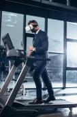 Seitenansicht der Geschäftsmann im Anzug und virtual-Reality-Kopfhörer auf Laufband im Fitness-Studio trainieren