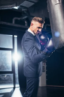 handsome businessman in suit grimacing while boxing in gym