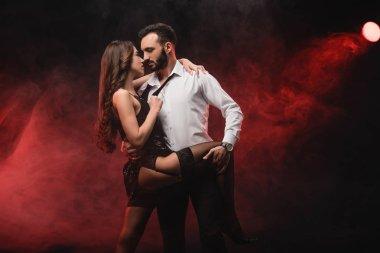 Heterosexual passionate couple hugging in red smoky room stock vector