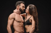 Fotografie beautiful woman hugging sexy shirtless man isolated on black