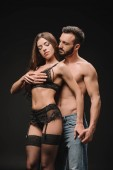 Fotografie sexy man hugging girlfriend in lingerie isolated on black