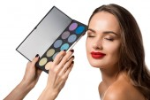 oříznutý pohled ženy drží paletu s eyeshadows a které tvoří krásnou dívku se zavřenýma očima izolované na bílém