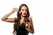 attractive girl in black dress applying powder on face with cosmetic brush isolated on white