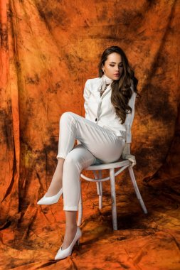 Attractive girl with long hair in white suit sitting on chair on textured background stock vector