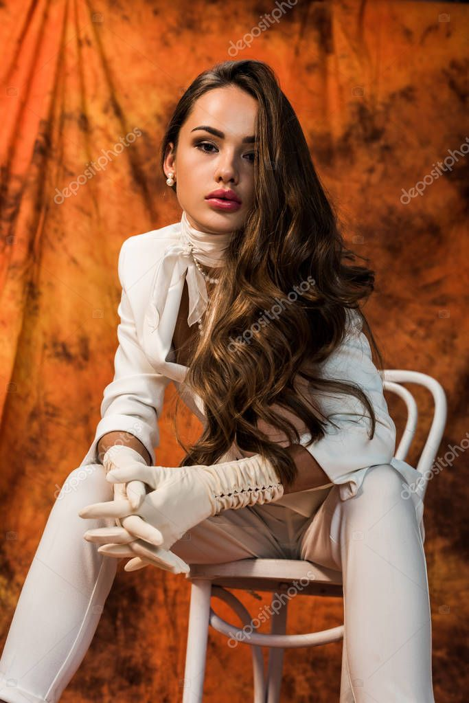 Attractive girl with long hair in white suit sitting on chair and looking at camera on textured background stock vector
