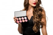 Fotografie cropped view of girl in black dress with red lips holding palette with eyeshadows isolated on white