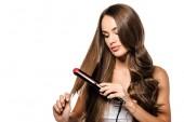 atraktivní dívka drží vlasy a pomocí žehličky izolované na bílém