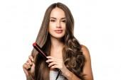 Fotografia bella ragazza con capelli marroni lunghi utilizzando raddrizzatore e guardando la macchina fotografica isolata su bianco