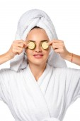 krásná dívka v županu drží plátky okurky poblíž oči a úsměv, izolované na bílém