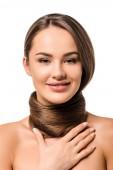 Fotografia ragazza attraente con capelli marroni lunghi intorno al collo che guarda lobbiettivo e sorridente isolato su bianco