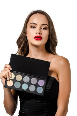 attractive girl holding palette with eyeshadows and looking at camera isolated on white