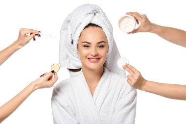 cropped view of women holding cosmetic accessories and beautiful girl in bathrobe isolated on white