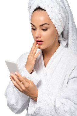 Surprised girl in bathrobe looking at smartphone screen isolated on white stock vector