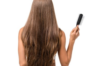 back view of girl with long brown hair holding hairbrush isolated on white