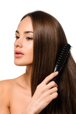 beautiful girl combing long hair with hairbrush isolated on white