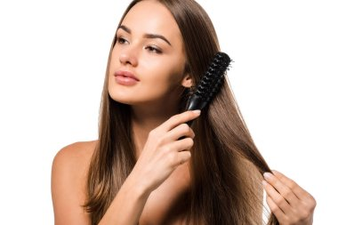 attractive girl combing long brown hair with hairbrush isolated on white