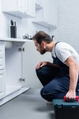 Fotografie konzentriert bärtigen Handwerker mit Toolbox, die Überprüfung der Spüle in der Küche