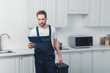 serious bearded repairman in working overall holding toolbox and looking at clipboard in kitchen at home