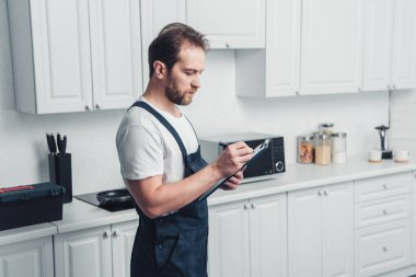 adult repairman in working writing in clipboard in kitchen at home