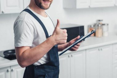 partial view of handyman holding clipboard and doing thumb up gesture in kitchen