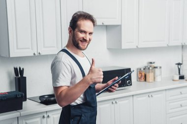 smiling handsome adult bearded repairman holding clipboard and doing thumb up gesture in kitchen
