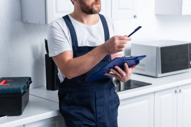 partial view of bearded craftsman pointing by pen and holding clipboard in kitchen