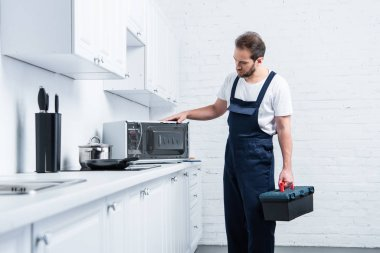 adult handyman with toolbox checking microwave oven in kitchen